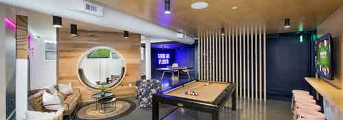 AMLI Lenox game room with pool table and ping pong table and television with multiple seating areas and wooden walls