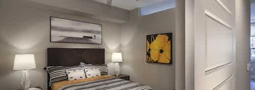 A bedroom of an apartment at AMLI Riverfront Green with art work and lamps and partial view of sliding bedroom door