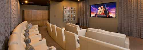 Interior view of AMLI RidgeGate media room with 3 rows of theater-style seating and centered wall mounted large flat screen