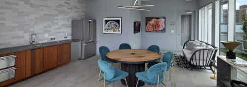 Interior view of AMLI Park Broadway rooftop lounge with catering kitchen and a variety of seating and flat screen TV