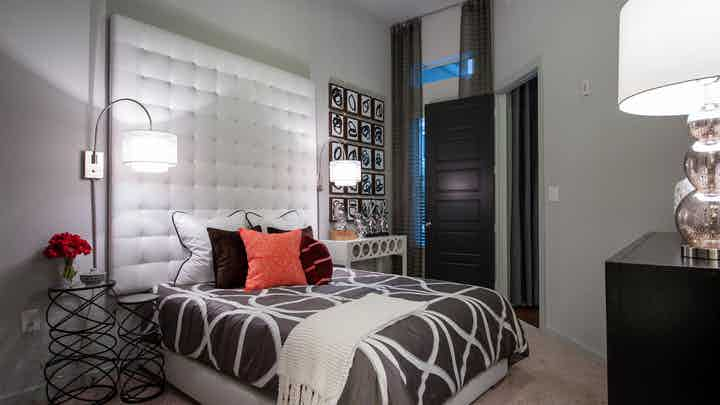 AMLI Uptown apartment bedroom with bed, white cushioned wall, unique nightstands and overhead lamps and tall window