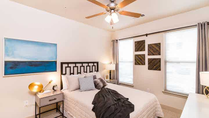 Interior view of a bedroom at AMLI Inverness with a bed with black metal headboard and a blue painting on the wall and lamps
