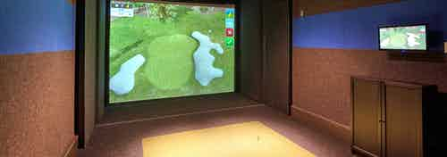 Indoor golf simulator amenity at AMLI Deerfield with simulated course image on large screen and smaller navigation screen