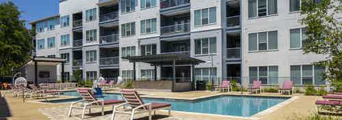 Daytime view of AMLI South Shore main pool with surrounding burgundy lounge chairs and a view of building facade