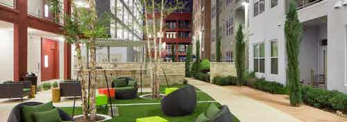 Courtyard at AMLI at Mueller with seating area on a grassy square in the center of surrounding pavement and shrubbery