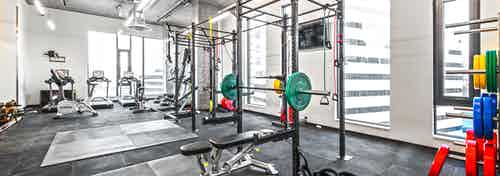 Interior Fitness Center of AMLI Arc with free standing weights squat racks with colorful weights and cardio equipment
