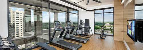 Upstairs AMLI Lenox exercise room with treadmills and weights and fitness on demand with floor to ceiling windows