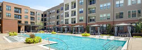 AMLI Addison apartment building pool with private cabanas and outdoor entertainment area and lounge seating and lush planters