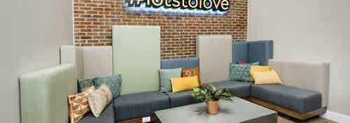AMLI Decatur dog lounge with comfortable seating and table with plant on it with a #lotsoflove sign hanging on brick wall