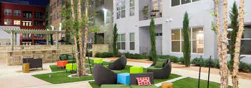 Daytime view of AMLI at Mueller courtyard with black lounge chairs and colorful foot rests on squares of grass in the center