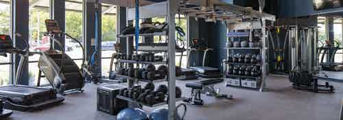 24 hour fitness zone at AMLI South Shore apartments with blue walls featuring cardio and weigh training machines and dumbbells