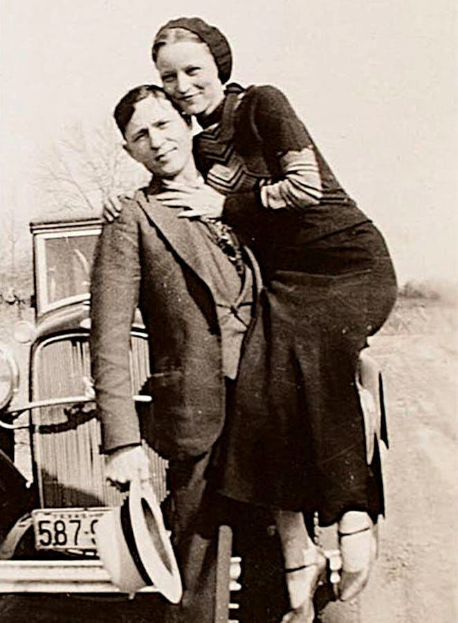 Clyde Barrow and Bonnie Parker smiling for a photo in front of their car