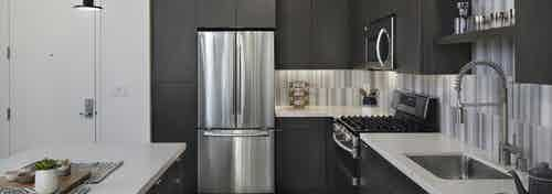 Interior of AMLI Park Broadway kitchen with gray wood floors and stainless steel appliances and designer tile backsplash
