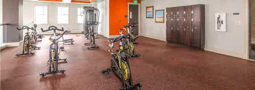 Interior of the spinning and yoga room at AMLI Doral with orange wall accent color and lockers