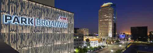 Aerial view of AMLI Park Broadway apartment building monument sign lit up with a view of lit street and city buildings