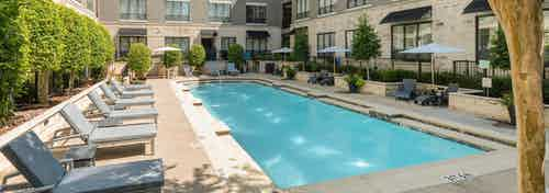 Second courtyard pool at AMLI Las Colinas apartments with surrounding gray lounge chairs and umbrellas and green shrubs
