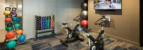 AMLI on Aldrich fitness center featuring colorful kettlebells and exercise balls with two exercise machines in front of a TV