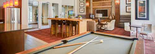 Clubhouse view at AMLI Interlocken apartments with a pool table multiple seating areas and a fireplace in the background