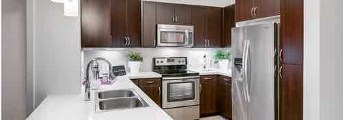Interior view of a kitchen at AMLI Cherry Creek apartments with espresso colored cabinets and white granite counter tops