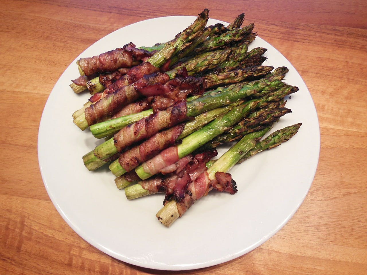 White plate full of bacon-wrapped asparagus