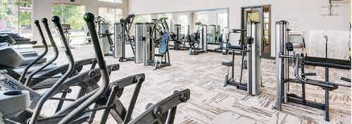 A fitness center at AMLI Cherry Creek apartments with strength training machines and treadmills and elliptical machines