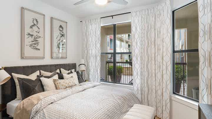 Bedroom at AMLI Quadrangle with a short grey headboard with white bedding and white walls with 2 large windows with blinds