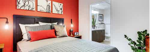 Interior view of a bedroom at AMLI Cherry Creek apartments with a bed backing up to a bright orange wall and view of bathroom
