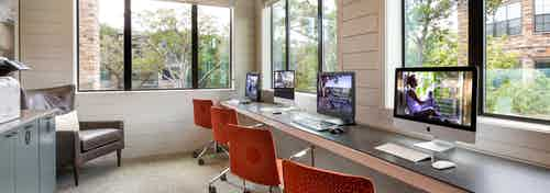 Daytime interior view of AMLI Covered Bridge's well-lit resident business center with four desktop monitors