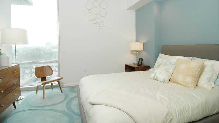 AMLI on 2ND bedroom with a blue geometric carpet and floor to ceiling window panel and light blue accent wall behind a large white bed