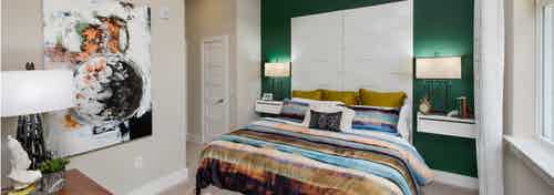 AMLI Buckhead bedroom with emerald accent wall and teal, coral and olive striped bedding with window to the right of the bed
