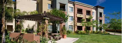 Exterior daytime view of AMLI Warner Center apartment trellis with greenery, grill station picnic area in open grass area
