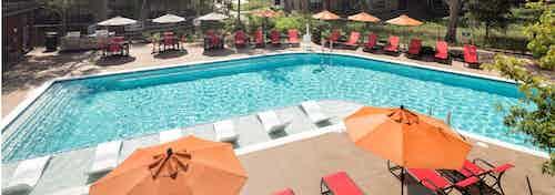 Daytime view of AMLI Covered Bridge pool with orange umbrellas, red lounge chairs, and lush surrounding greenery