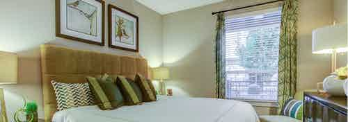 A bedroom at AMLI Riverfront Park apartments with lamps and artwork and a window with green curtains and a balcony view