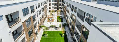 Aerial view of AMLI Quadrangle landscaped courtyard with wood pergolas and ample seating and large grassy area with trees