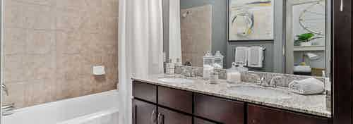 Interior view of bathroom with dark double vanity with granite counters and wall mirror and soaking tub at AMLI Parkside