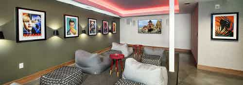 AMLI Lenox theater room with bright pink ceiling lights and big screen TV and multiple bean bag chairs with colorful artwork