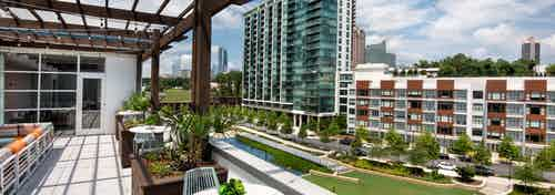 AMLI Buckhead skydeck with a pergola for seating area and a view of vibrant grass and modern buildings under a cloudy sky