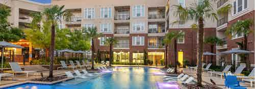 Dusk exterior view of pool area at AMLI Frisco Crossing apartments with lounge seating and umbrellas and palm trees