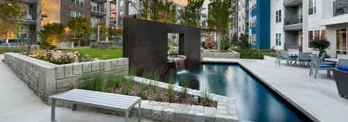 Exterior view of an outdoor fountain in the middle of AMLI Piedmont Heights apartment courtyard in between its buildings