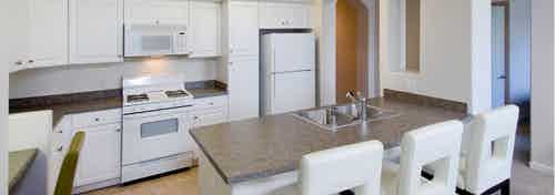 Interior view of AMLI Warner Center vacant apartment kitchen with white cabinetry and white appliances and white bar stools