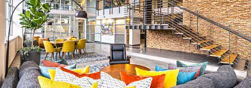 AMLI Mark24 two-story lobby with cozy seating areas and stone wall behind metal staircase and glass door and windows in rear