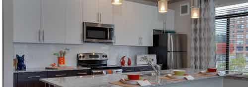 AMLI Ponce Park kitchen with stainless steel microwave nested in white cabinets above an oven nested in dark lower cabinets
