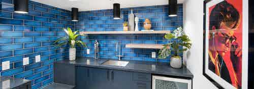 AMLI Lenox amenity kitchen area with blue tiled walls and sink and refrigerator and bright painting on the wall