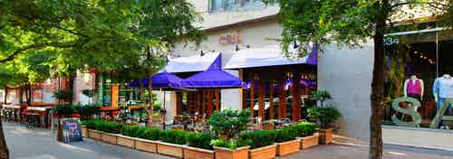 AMLI Downtown exterior showing mannequins in a retail shop window and an outdoor dining area with blue umbrellas and shrubs