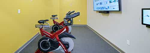 Bright yellow walls behind two spin bikes facing fitness on demand TV at fitness center at AMLI Bellevue Park apartments