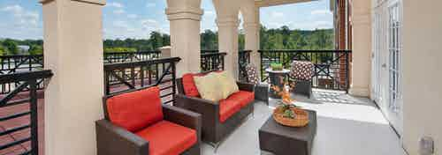Spacious patio area at AMLI North Point with red wicker lounge chairs fenced in with scenic views in the background