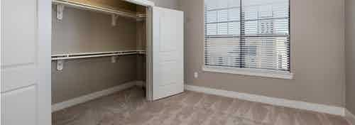 Interior of AMLI Eastside bedroom with open doors revealing spacious closet with grey walls and a window with daytime view