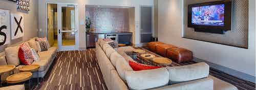 Interior view of the media room at AMLI Denargo Market apartments with large couches a small fridge and large television