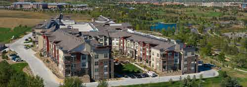 Birdseye view of AMLI Interlocken apartments view of the entire complex with a very large grassy area in with trees and lake