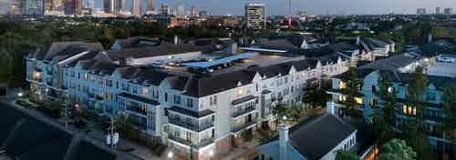 Nighttime aerial view of AMLI Memorial Heights apartment building with cars parked on rooftop and cityscape in background